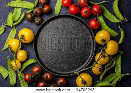 Food background with copy space. Red and yellow tomatoes and green pea around epty black cast iron plate. Top view, for text