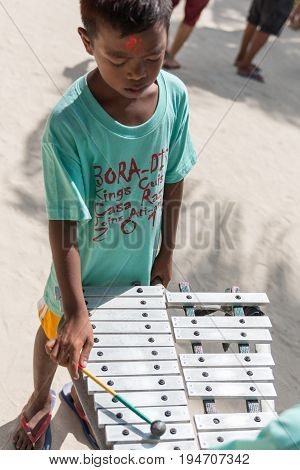 BORACAY, WESTERN VISAYAS, PHILIPPINES - JANUARY 11, 2015: Native filipino boy playing music during Ati-Atihan Festival at White Beach.