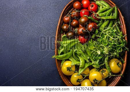 Red and yellow tomatoes, watercress salad and green pea on try. Harvest or clean healthy eating concept, copy space