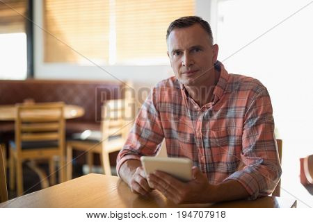 Portrait of man using digital tablet in restaurant