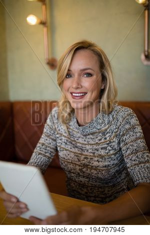 Portrait of smiling beautiful woman using digital tablet at table in bar