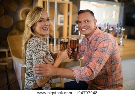 Portrait of happy couple having beer at bar counter