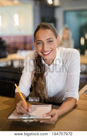 Portrait of smiling bartender writing on clipboard at bar counter