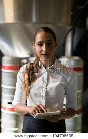 Portrait of waitress using digital tablet in bar