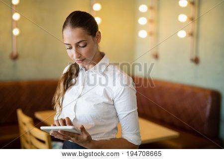 Beautiful waitress using digital tablet in bar