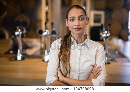 Portrait of female bartender standing with arms crossed in bar