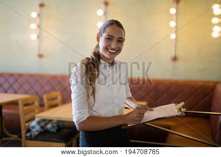 Portrait of female bartender writing on clipboard at bar counter