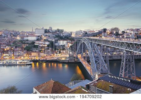 View of the sunset at the city of Porto Dom Luis bridge and Douro river Portugal.