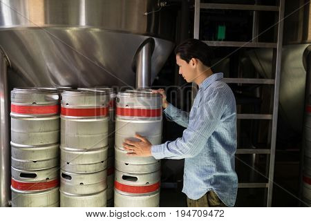 Manager checking beer keg in warehouse of restaurant