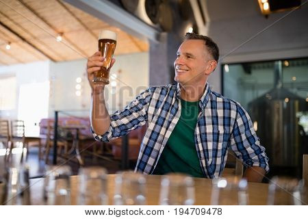 Smiling man having glass of beer at counter in bar
