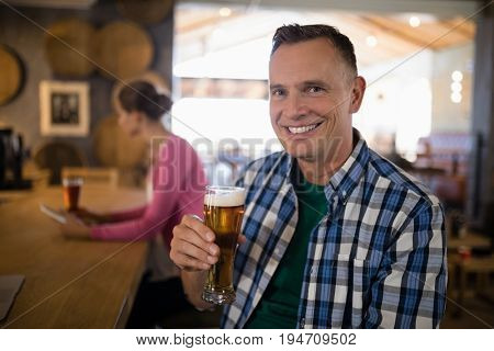 Portrait of smiling man having glass of beer at counter in bar