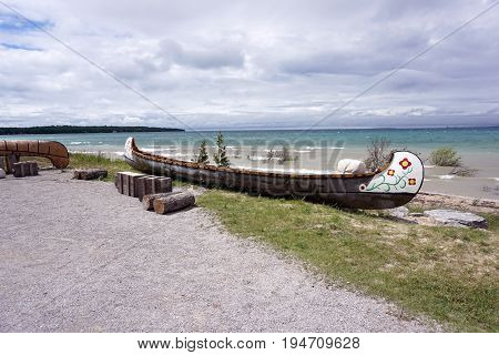 MACKINAW CITY, MICHIGAN / UNITED STATES - JUNE 18, 2017: A large birch bark canoe sits outside the north entrance of Fort Michilimackinac, at the Colonial Michilimackinac State Park.