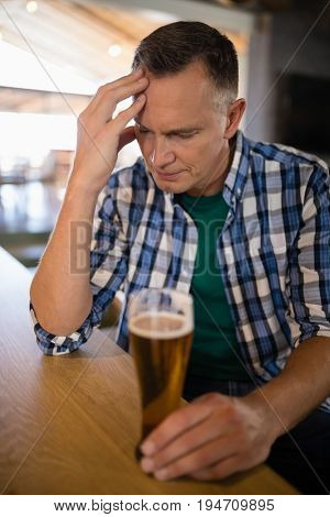 Worried man sitting at bar with glass of beer at bar counter