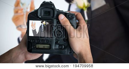 Cropped image of hands holding camera  against midsection of bridegroom holding champagne flute