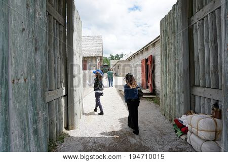 MACKINAW CITY, MICHIGAN / UNITED STATES - JUNE 18, 2017: Visitors walk through the north entrance into Fort Michilimackinac, in the Colonial Michilimackinac State Park.