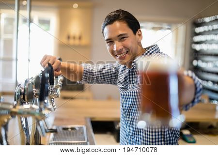 Portrait of bar tender offering glass of beer to customer at bar counter in restaurant