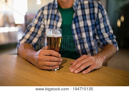 Mid section of man sitting with glass of beer at bar counter