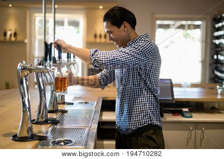 Bar tender filling beer from beer pump at bar counter in restaurant