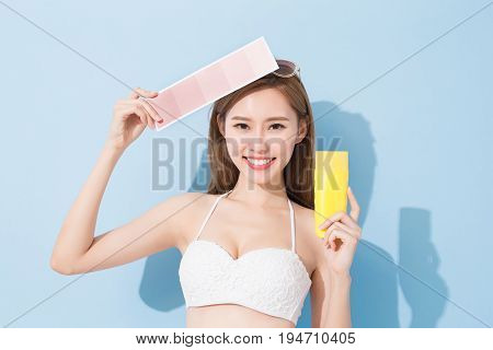 woman take skin color scale and sunscreen on the blue background