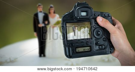 Cropped hand of photographer holding camera  against wedding cake figurine