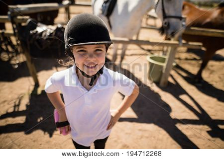 Portrait of girl standing with hands on hips in the ranch