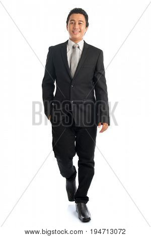 Full length front view portrait of handsome young Southeast Asian businessman walking, isolated on white background.