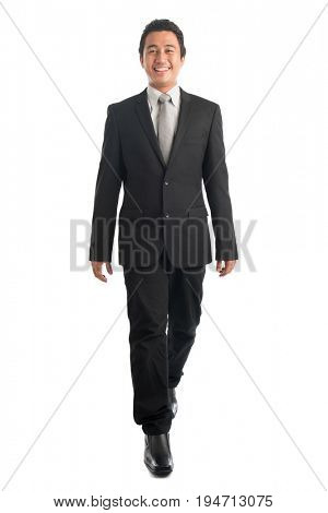 Full body front view portrait of smart young Southeast Asian businessman walking, isolated on white background.