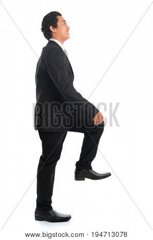 Full body side view of attractive young Southeast Asian businessman stepping up stair case, isolated on white background.