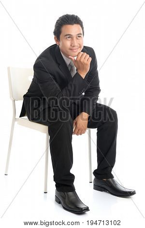 Full body portrait of attractive young Southeast Asian businessman sitting on a chair and thinking, isolated on white background.