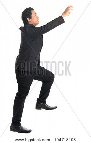 Full body side view of young Southeast Asian businessman stepping up stair case and hand grabbing something, isolated on white background.