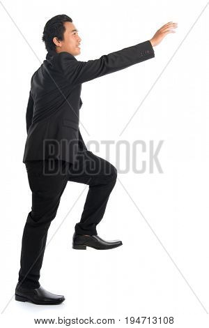 Full body side view of attractive young Southeast Asian businessman stepping up stair case and hand reaching something, isolated on white background.