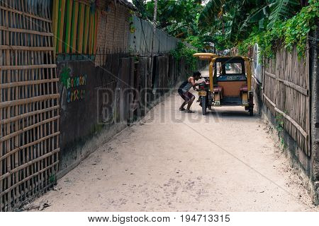 BORACAY, WESTERN VISAYAS, PHILIPPINES - JANUARY 12, 2015: Native filipino fixing his tuk tuk in a narrow passageway that goes to Bulabog Beach