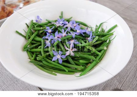 French green beans with edible blue borage flowers and garlic in a white bowl
