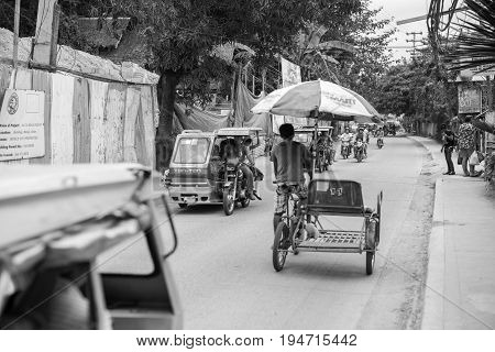 BORACAY, WESTERN VISAYAS, PHILIPPINES - JANUARY 12, 2015: Black and white picture of tuk tuk motorcycles and a man riding bicyle