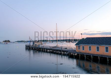 Boathouse and dock in the calm and beautiful Boothbay Harbor at dusk