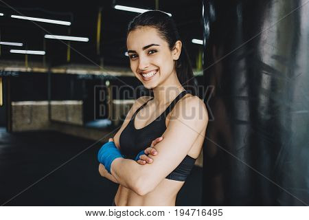 Beautiful young woman standing with crossed arns in gym in front of the camera and smiling. She is happy because she has won in a girls fighting competition. Close up