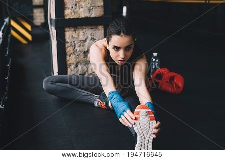 Beautiful slim and sporty girl doing stretching exercises sitting on th floor in th gym. Serious girl is warming up before the training or boxing. Close up