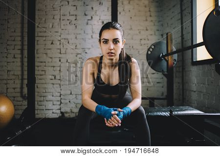 Young slim and weary female sitting on the bench in the gym near the window in front of the camera and having her rest after intensive boxing training. Close up