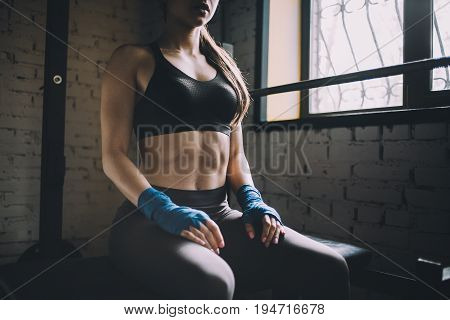 Pretty and confident sportive girl sitting on the bench in gym and morally preparing for fighting. She has put her hands on th lap. Close up
