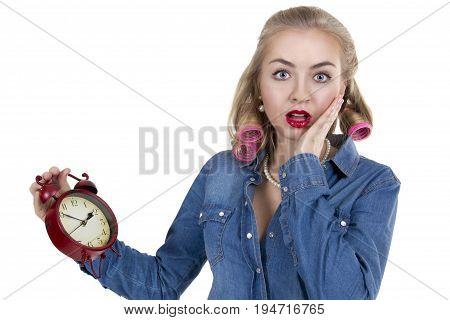 Frightened young woman in curlers with alarm clock