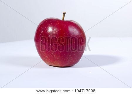 Ripe red apple on a white clean table
