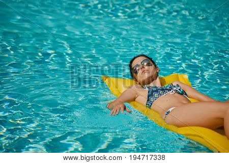Young happy woman relaxing in a swimming pool