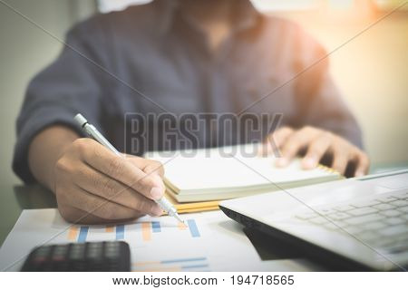 Young businessmen analyze graphs and take notes to meet goals set over blurred office.Film tones and Light fair