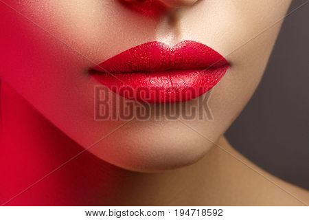 Cosmetics makeup and trends. Bright lip gloss and lipstick on lips. Closeup of beautiful female mouth with red lip makeup. Beautiful part of female face. Perfect clean skin in red light