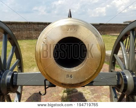large brass cannon on wheels with JWR and 34 on it