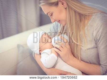 Young mother feeding her little precious baby from the bottle, healthy child's nutrition, special milk formula, happy family life