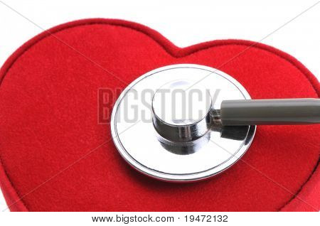 White background vertical studio image of monitoring heart concept with stethoscope and red heart