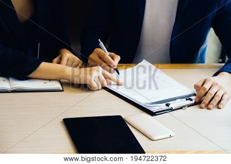 Businessman and businesswoman signing paper (insurance contract important)