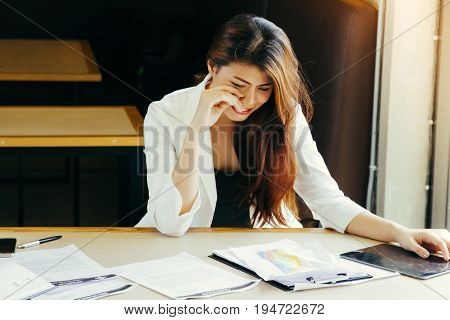 Desperate sad young businesswoman working at the office desk.