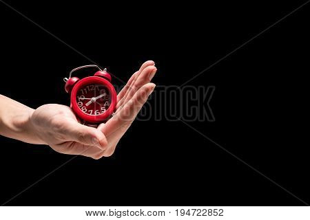 Male hand holding red alarm clock on a black background. Free space for text